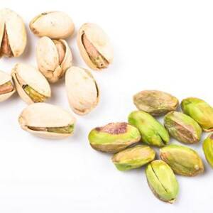 Several pistachio nuts naked and in shell close up isolated on white